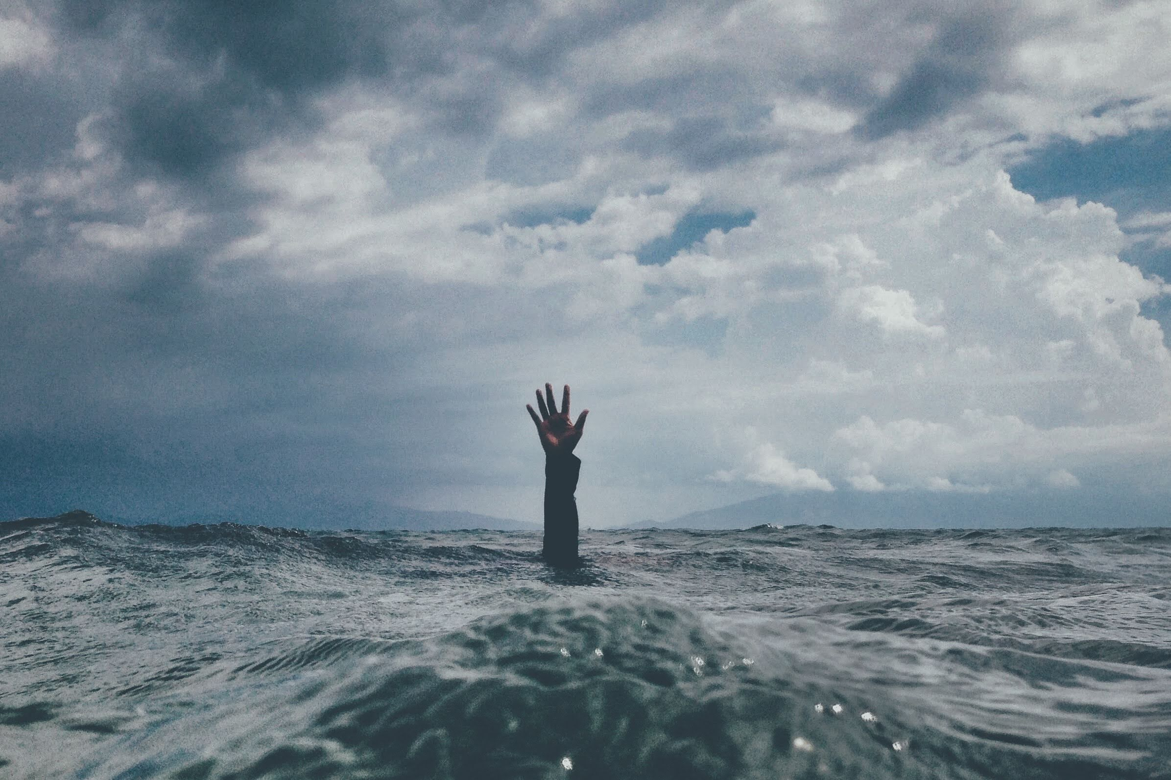 Hand coming out of the water in search for help. Image for mental health article post covid
